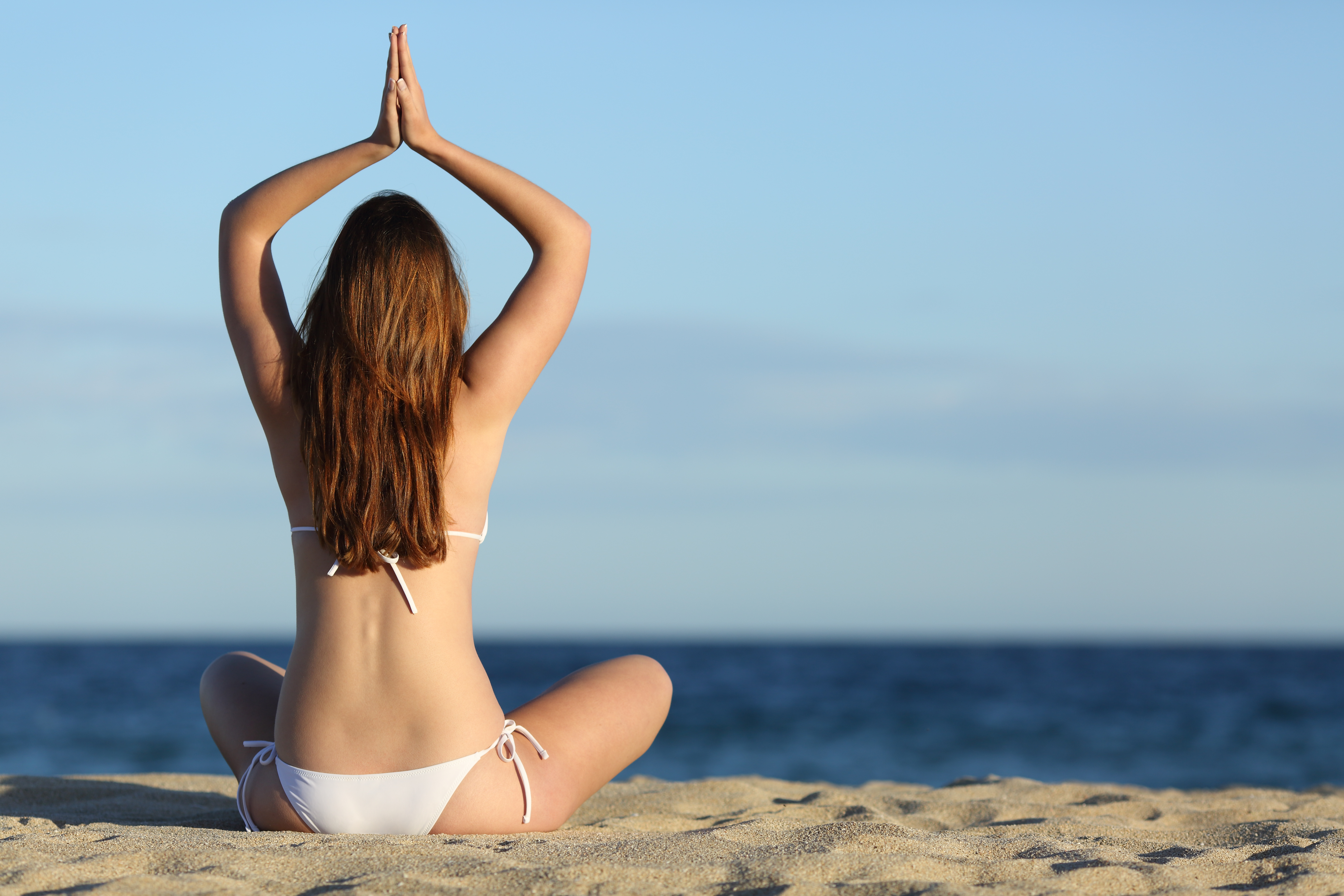 Woman practicing yoga exercises on the beach in summer